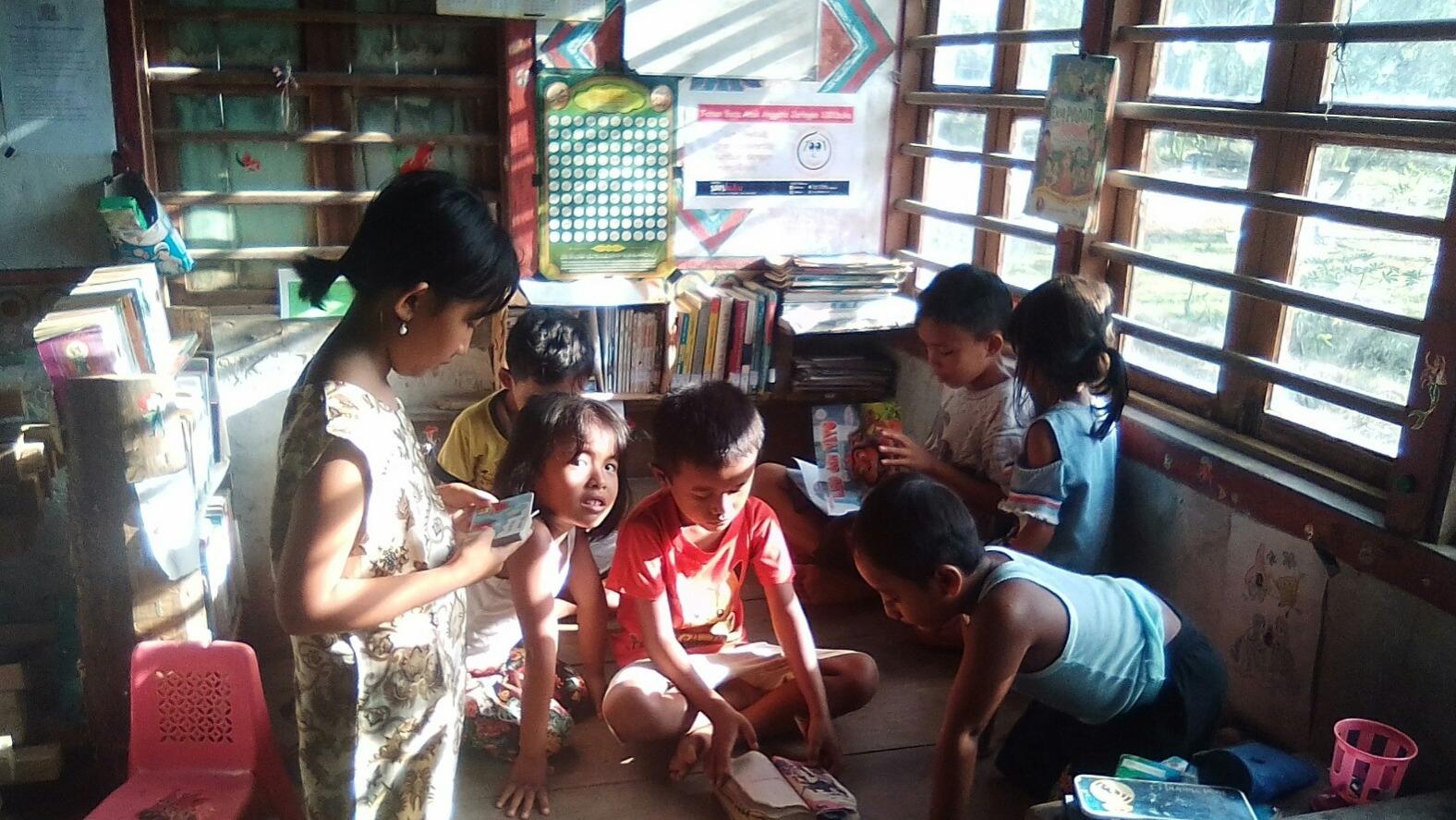 Membangun Pojok Baca untuk menyebarkan virus baca terhadap anak.